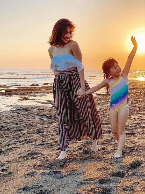 Keduanya menikmati suasana pantai di sore menjelang malam hari. Tanpa mengenakan alas kaki, dengan leluasa Gisel menemani sangbuah hati bermain pasir di tepi pantai. Ekspresi menggemaskan Gempi juga terlihat di foto ini. (Instagram/gisel_la)