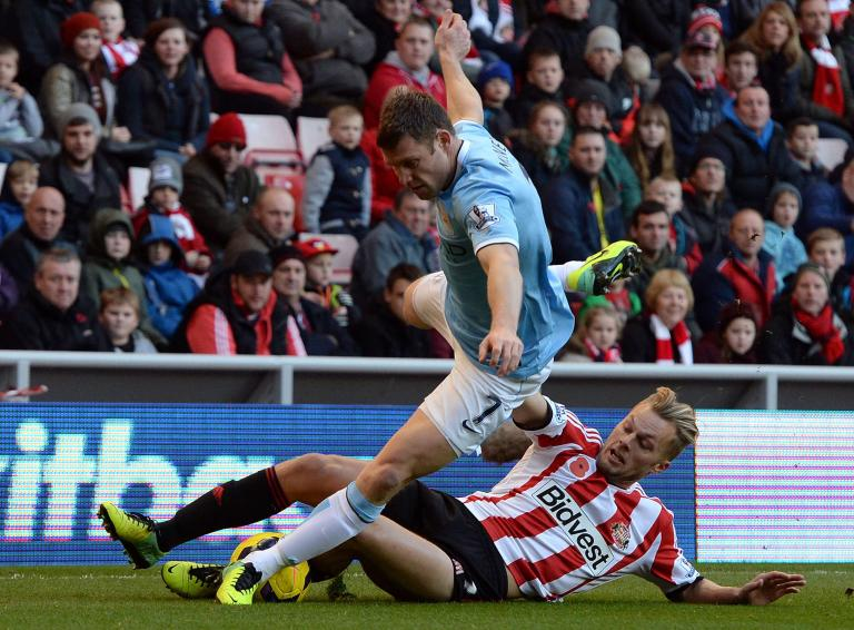 Sunderland's Larsson challenges Manchester City's Milner during their English Premier League soccer match in Sunderland