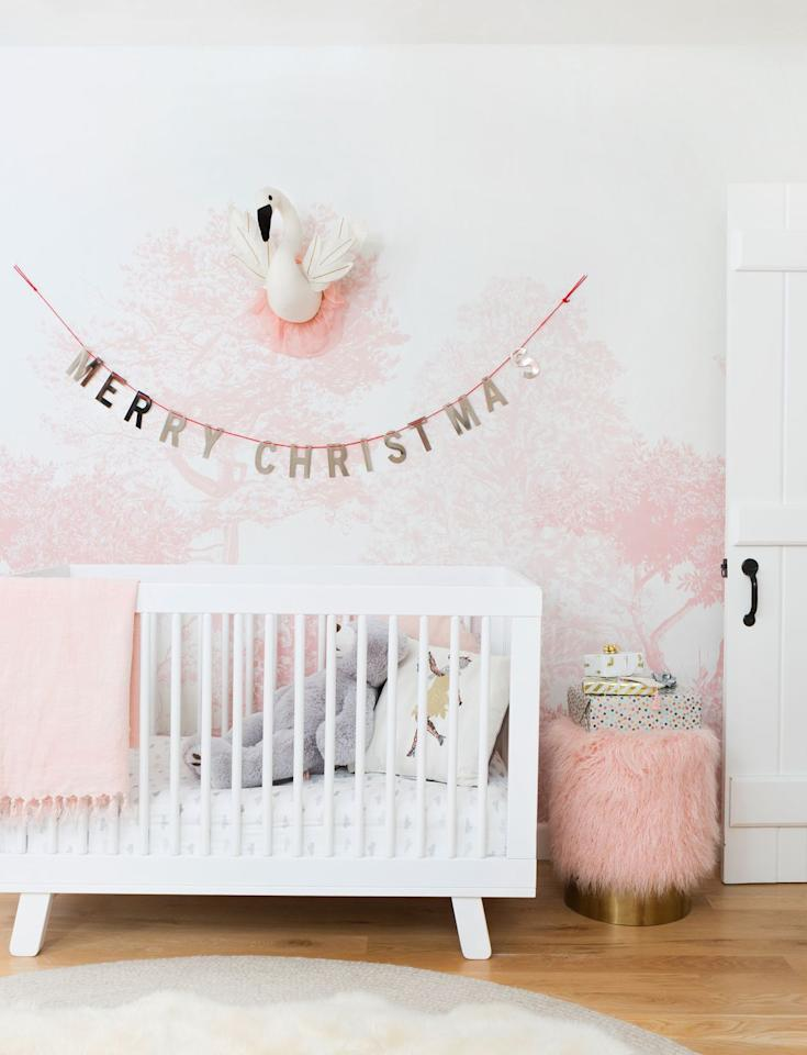 """<p>Use your words with a metallic paper garland that says, """"Merry Christmas!"""" If it's baby's first Christmas, this is a great way to deck out their room without breaking away from the current color palette. <a href=""""https://stylebyemilyhenderson.com/"""" target=""""_blank"""">Emily Henderson</a> hung one right above the crib here. </p><p><a class=""""body-btn-link"""" href=""""https://go.redirectingat.com?id=74968X1596630&url=https%3A%2F%2Fwww.etsy.com%2Flisting%2F192798869%2Fchristmas-decor-christmas-garland-gold&sref=https%3A%2F%2Fwww.housebeautiful.com%2Fentertaining%2Fholidays-celebrations%2Fg3957%2Fchristmas-garlands%2F"""" target=""""_blank"""">BUY NOW</a> <strong><em>Gold Christmas Garland, $9</em></strong></p>"""
