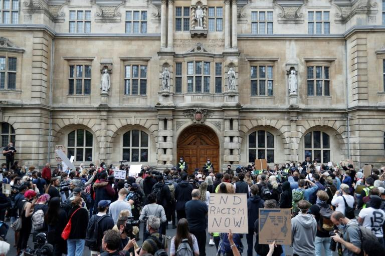 "Protesters chant ""Take it down!"" and ""Decolonise!"", and held placards urging ""Rhodes Must Fall"" and ""Black Lives Matter"" in front of the imperialist's statue at Oxford's Oriel College"