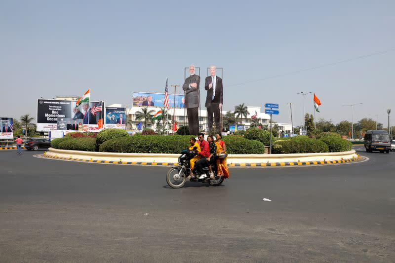 A family ride a scooter in front of cutouts of India's Prime Minister Narendra Modi and U.S. President Donald Trump along a road, ahead of Trump's visit, in Ahmedabad