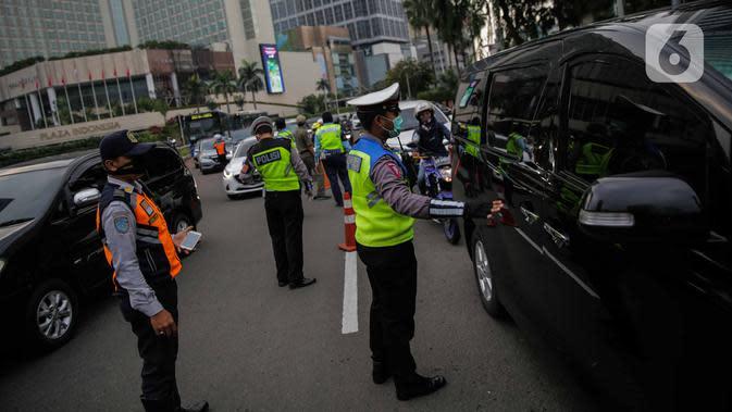 Petugas gabungan dari Polisi, Dishub, dan Satpol PP mengimbau pengguna kendaraan saat melakukan Pengawasan Pelaksanaan PSBB di Bundaran HI, Jakarta, Senin (13/4/2020). Dalam pengawasan tersebut petugas mengimbau masyarakat untuk menggunakan masker saat berpergian. (Liputan6.com/Faizal Fanani)