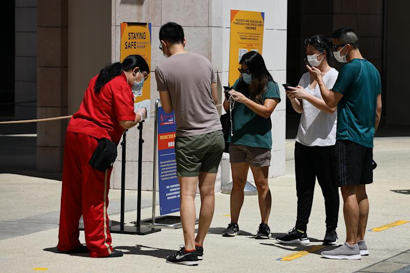 SINGAPORE - JULY 03: Visitors wearing protective mask scan a QR code for Safe Entry check-in at the Universal Studios at Resorts World Sentosa on July 3, 2020 in Singapore. From July 1, Universal Studios Singapore reopened its door to visitors but operating capacity is limited to no more than 25 per cent as Singapore further eased the coronavirus (COVID-19) restrictions. Universal Studios is among the 13 key attractions to resume its operation in stages with safe management measures in place. As of July 3, the total number of COVID-19 cases in the country stands at 44,479. (Photo by Suhaimi Abdullah/Getty Images)