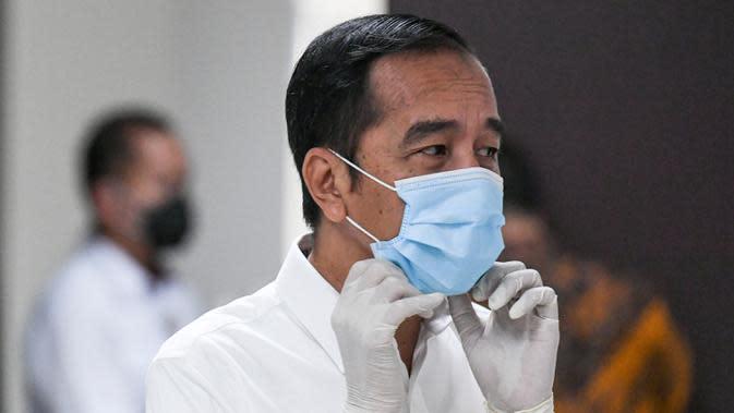 Presiden Joko Widodo merapihkan masker yang digunakannya saat meninjau Rumah Sakit Darurat Penanganan COVID-19 Wisma Atlet Kemayoran, Jakarta, Senin (23/3/2020). Dalam kunjungannya Jokowi memastikan Rumah Sakit Darurat siap digunakan untuk menangani 3.000 pasien. (ANTARA FOTO/Hafidz Mubarak A/Pool)
