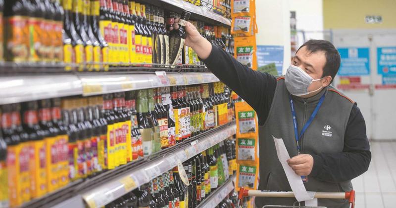 2月21日,山西太原超市工作人員根據網路訂單挑選調味品。(圖/中新社)