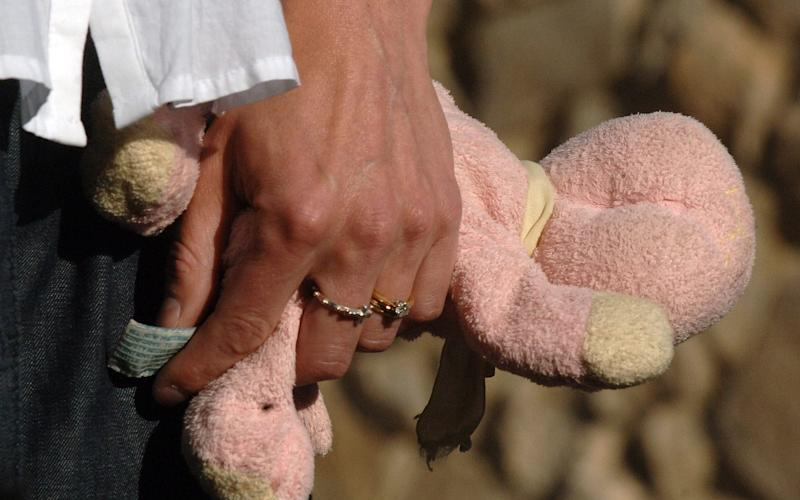 Kate and Gerry McCann in Praia da Luz, holding a stuffed toy that belonged to daughter Madeline - EDDIE MULHOLLAND