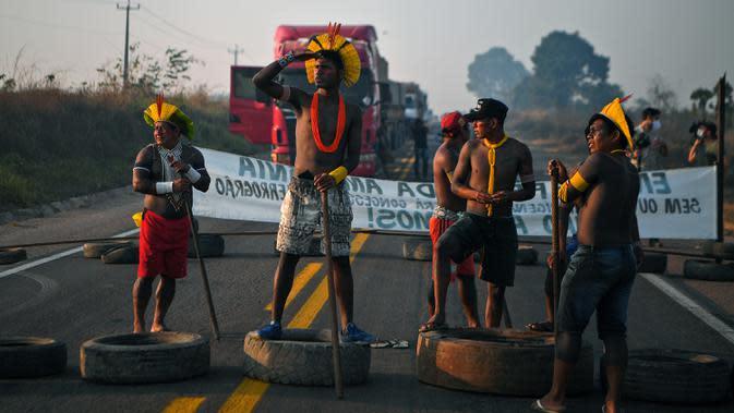 Masyarakat suku Kayapo saat memblokir jalan raya utama Trans-Amazonian dengan melakukan barikade menggunakan ban bekas di Novo Progresso di Negara Bagian Para, Brasil (17/8/2020). (AFP Photo/Carl De Souza)