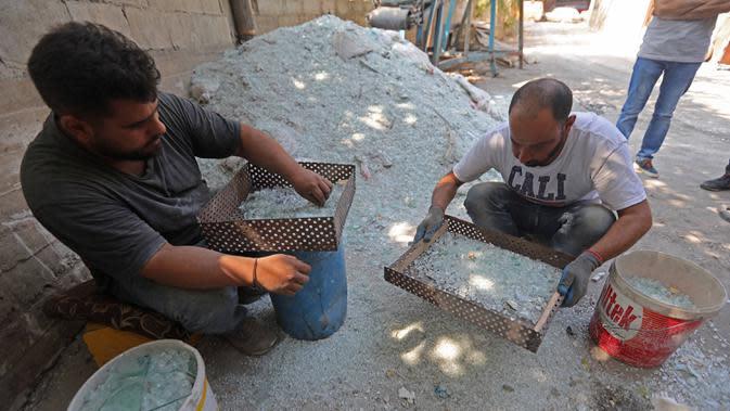 Para pekerja menyaring pecahan kaca di sebuah pabrik kaca di Tripoli, Lebanon, 12 September 2020. Kaca-kaca dari bangunan yang rusak akibat ledakan Beirut didaur ulang oleh warga setempat untuk dijadikan barang pecah belah. (Xinhua/Bilal Jawich)
