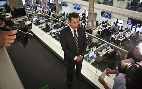 Ehab Al Shihabi, interim CEO for Al-Jazeera America, listens during an interview overlooking the newsroom, after the network's first broadcast on Tuesday, Aug. 20, 2013 in New York. The Qatar-based Al-Jazeera Media Network launched its U.S. outlet only eight months after announcing the new venture, which on Tuesday replaced Al Gore's Current TV in more than 45 million TV homes. (AP Photo/Bebeto Matthews)