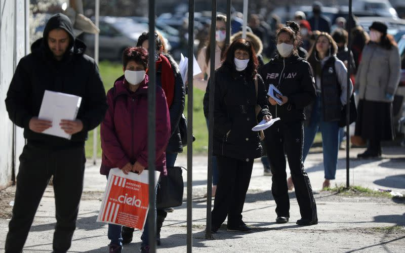 FILE PHOTO: People wearing face masks in attempt to prevent the spread of coronavirus disease (COVID-19) wait outside a labour office in Sofia