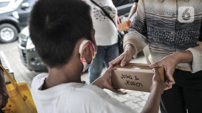 Seorang anak menerima donasi ponsel yang diberikan oleh Komunitas #WartawanLintasMedia saat acara #PonselPintarUntukPelajar di Jakarta, Minggu (9/8/2020). (merdeka.com/Iqbal S. Nugroho)