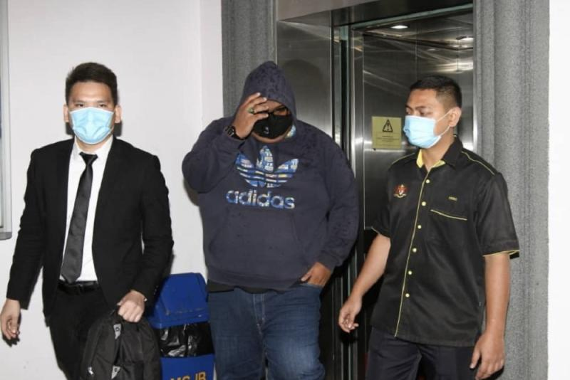 Policeman Mohd Yusri Borhan (centre) pleaded not guilty at the Johor Baru Sessions Court today to two charges of soliciting and receiving bribes worth RM3,500 more than four years ago. — Picture by Ben Tan