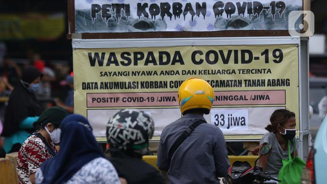 Warga melihat tanda peringatan bahaya COVID-19 di sekitar Pasar Blok A Tanah Abang, Jakarta, Selasa (1/9/2020). Guna meningkatkan kewaspadaan masyarakat, muspida kecamatan Tanah Abang memajang peti mati dilengkapi data jumlah korban COVID-19 di wilayah tersebut. (Liputan6.comHelmi Fithriansyah)