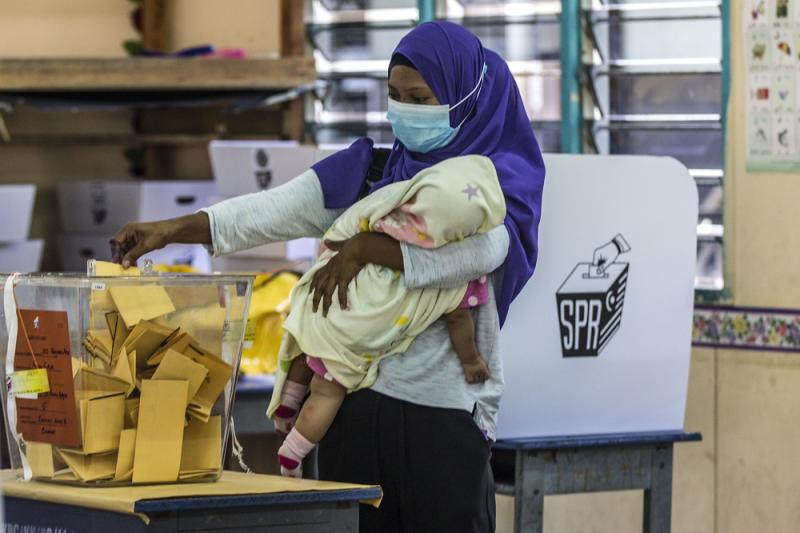 A voter cradles her child as he casts her vote at SK Pulau Gaya September 26, 2020. — Picture by Firdaus Latif