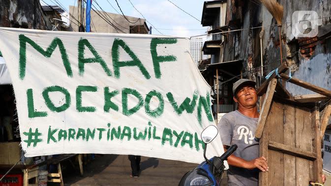 Warga berjalan di salah satu gang yang ditutup secara mandiri di kawasan Tambora, Jakarta, Sabtu (4/4/2020). Penutupan akses masuk kawasan ini untuk membatasi kegiatan warga dan mencegah penyebaran serta penularan virus COVID-19. (Liputan6.com/Helmi Fithriansyah)