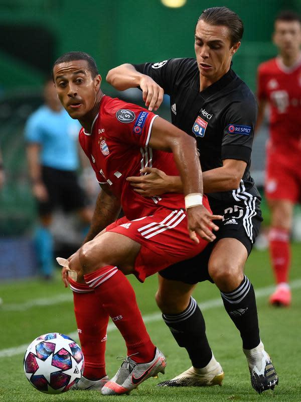 Gelandang Bayern Munchen, Thiago berusaha membawa bola dari kawalan gelandang Lyon, Maxence Caqueret pada pertandingan Semifinal Liga Champions di stadion Jose Alvalade di Lisbon, Portugal, Rabu, (19/8/2020). Munchen menang telak 3-0 dan melaju ke Final. (Franck Fife/Pool via AP)