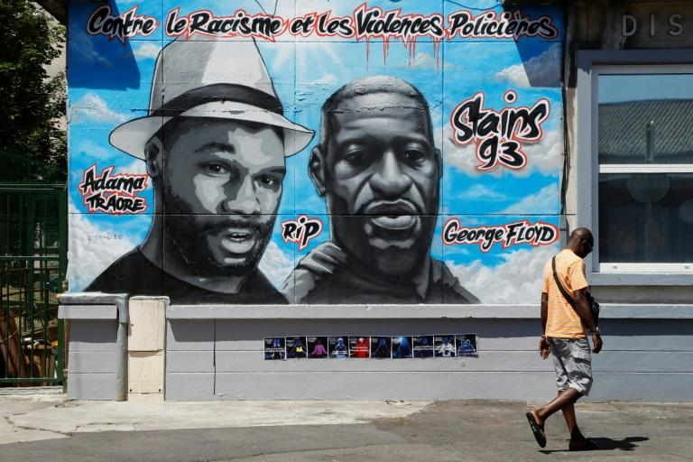 "A mural of Adama Traore, left, and George Floyd with the heading ""Against racism and police violence"" in Stains, a city outside Paris"