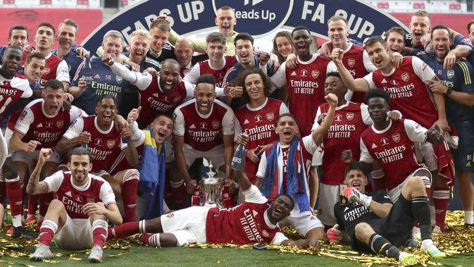 Striker Arsenal Pierre-Emerick Aubameyang, memegang trofi, dan rekan setimnya merayakan kemenangan 2-1 atas Chelsea pada final Piala FA di Stadion Wembley, Sabtu (1/8/2020). (Catherine Ivill / Pool via AP)