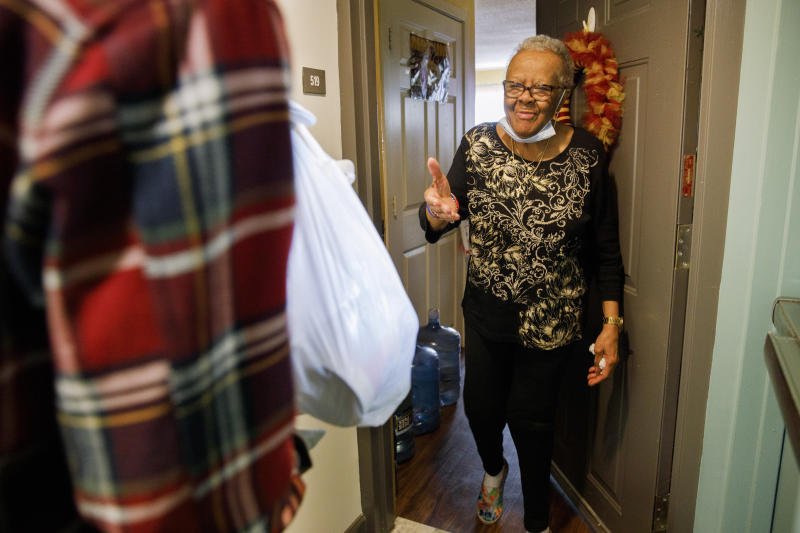 """Easter Brown, 77, of Washington, greets Michael Weber, with the nonprofit organization """"We Are Family DC,"""" as he delivers groceries to her apartment door, Saturday, March 21, 2020, in Washington. Seniors are being encouraged to stay in their homes due to the risk of the COVID-19 coronavirus. (AP Photo/Jacquelyn Martin)"""