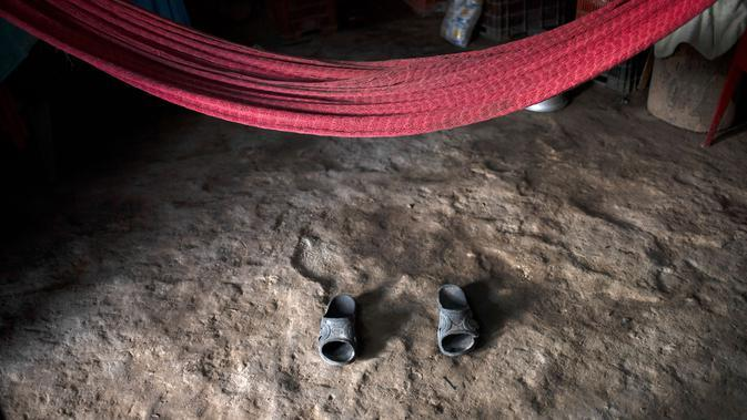 Pemandangan sepasang sandal di bawah tempat tidur gantung milik Joaquin Barrera, korban COVID-19, di rumahnya di Santiago Nonualco, El Salvador, 23 Juli 2020. Hingga 25 September 2020, kematian global akibat COVID-19 hampir mencapai satu juta, sepertiganya terjadi di Amerika Latin. (Yuri CORTEZ/AFP)