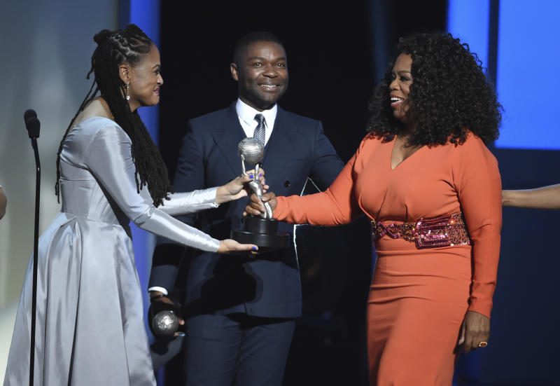 """FILE - In this Feb. 6, 2015 file photo, Ava DuVernay, from left, David Oyelowo, and Oprah Winfrey accept the award for outstanding motion picture for """"Selma"""" at the 46th NAACP Image Awards in Pasadena, Calif.  Hollywood's record in diversity and inclusion has improved in recent years, but it still lags behind the population — particularly in its executive ranks. (Photo by Chris Pizzello/Invision/AP, File)"""