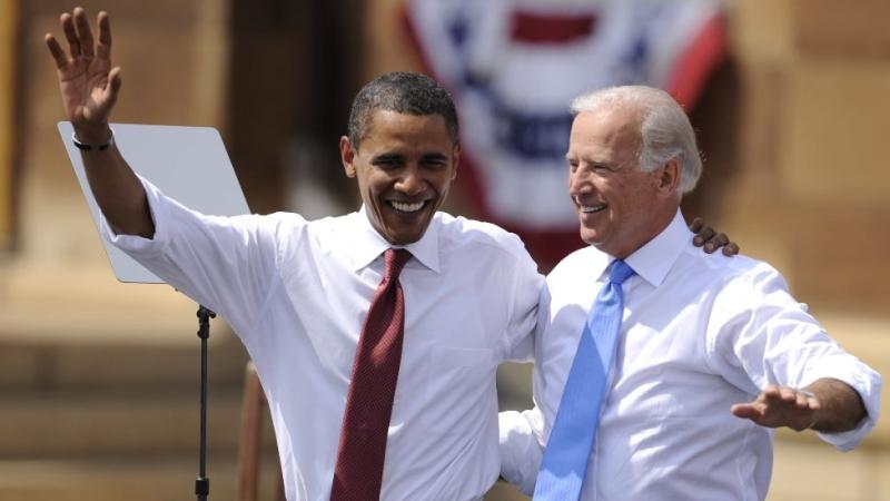 Barack Obama and Joe Biden wave while arm-in-arm.