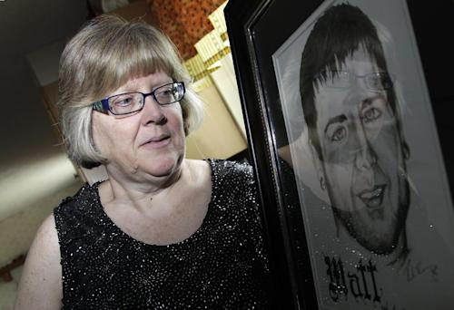 Jerri Jackson, mother of Aurora, Colo. theater shooting victim Matthew McQuinn, stands next to a sketch of her son in Springfield, Ohio on Sunday, July 14, 2013. Jackson remembers a conversation she had with her son, hours before the shooting. He talked about plans to move back to Ohio to work at a car parts factory near St. Paris; perhaps he would marry his girlfriend. He was homesick after struggling for a year to find full-time work in Colorado. Jackson offered to let him live with her to get started. Then McQuinn said he had to go. He was going to the movies. (AP Photo/Jay LaPrete)