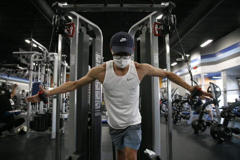 Benji Xiang, 32, wears a mask while working out at a gym in Los Angeles. Friday, June 26, 2020. With the coronavirus surging, at least four California counties on Friday paused or prepared to backtrack on their reopening plans in a bid to halt the spread of the virus. (AP Photo/Jae C. Hong)
