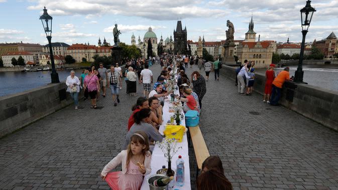 Warga menggelar makan malam di atas meja sepanjang 500 meter di jembatan bersejarah Charles Bridge di Praha, Republik Ceko, Selasa (30/6/2020). Kegiatan itu merupakan perpisahan simbolis yang digelar untuk menandai akhir dari masa krisis virus corona Covid-19 di negara tersebut (AP/Petr David Josek)