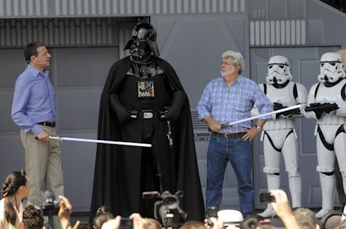"FILE - In this May 20, 2011 file photo, Disney CEO Robert Iger, left, and Star Wars creator George Lucas, third from right, talk to the Star Wars movie character Darth Vader, center, onstage at the Disney Hollywood Studios theme park during the re-opening celebration of the Star Tours motion simulation ride in Lake Buena Vista, Fla. Disney announced on Oct. 30, 2012 that it would buy Lucasfilm for $4.05 billion and resume making ""Star Wars"" movies, starting with Episode 7 in 2015. For Star Wars fans, the announcement has generated a lot of speculation about what direction the series will take. (AP Photo/Phelan M. Ebenhack, File)"