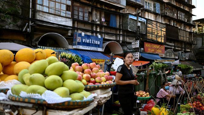 Seorang penjual buah menunggu pelanggan di sepanjang jalan di Hanoi (26/8/2020). (AFP Photo/Manan Vatsyayana)
