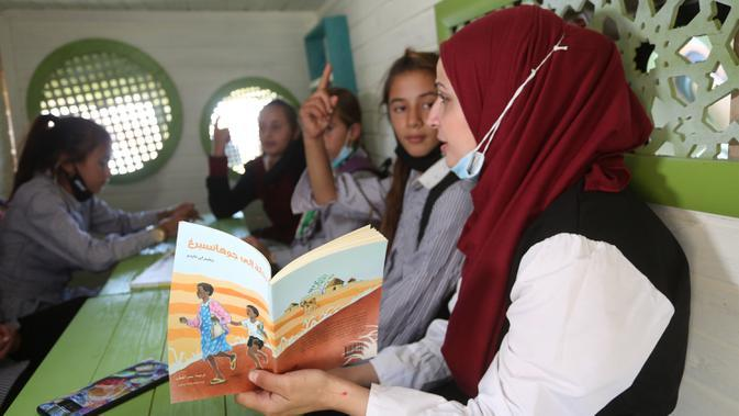 Para siswa Palestina duduk dalam bus yang telah dialihfungsikan menjadi ruang kelas keliling di Khirbet Ibziq, dekat Kota Tubas, Tepi Barat, 8 Oktober 2020. Sebuah asosiasi lokal mengalihfungsikan sebuah bus menjadi perpustakaan dan ruang kelas keliling. (Xinhua/Ayman Nobani)