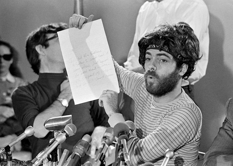 Jerry Rubin, one of the defendants in the Chicago 8 conspiracy trial, holds up a note that he said was written by Bobby Seale while he was gagged and manacled during trial session in Chicago on Thursday, Oct. 30, 1969. Rubin displayed the note during a news conference after a morning recess. (AP Photo/Jim Palmer)