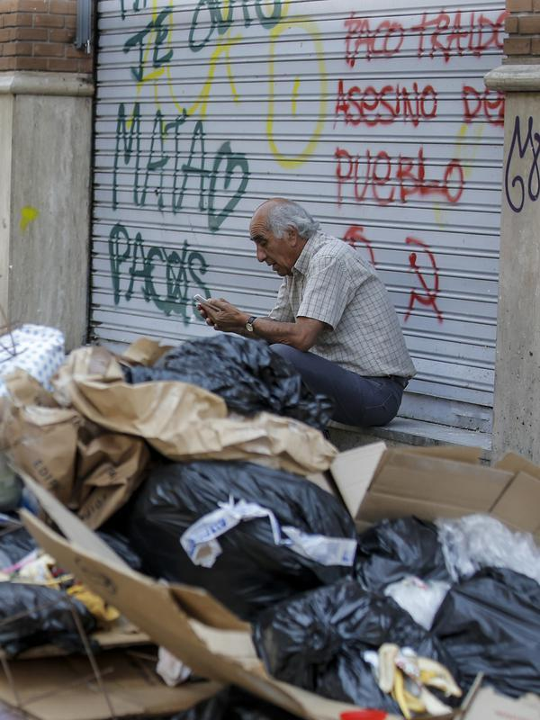 Seorang pria duduk di dekat tumpukan sampah di Santiago (14/11/2019). Protes kekerasan meletus di ibukota Chile, Santiago, pada Selasa ketika mata uang negara itu turun ke level terendah dalam sejarah. (AFP/Javier Torres)