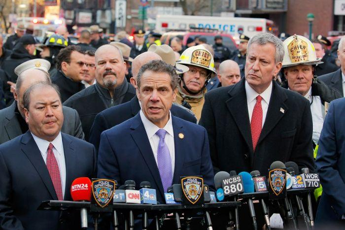 New York mayor Billl de Blasio looks on as New York governor Andrew Cuomo holds a press conference.