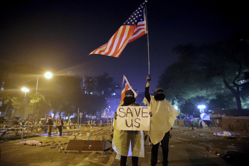 """FILE - In this Nov. 18, 2019, file photo, protesters hold British and American flags and a sign reading """"Save us"""" as they stand near Hong Kong Polytechnic University after police gave protesters an ultimatum to leave the campus in Hong Kong. From Tokyo to Brussels, political leaders have swiftly decried Beijing's move to impose a tough national security law on Hong Kong that cracks down on subversive activity and protest in the semi-autonomous territory. But the rhetoric from democratic nations has more bark than bite. (AP Photo/Kin Cheung, File)"""