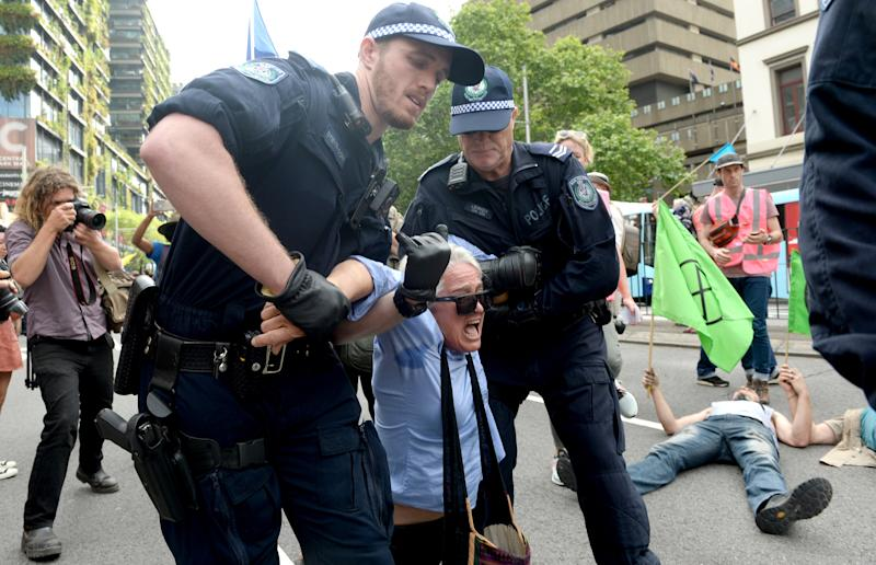 A protester being removed by two police officers during an Extinction Rebellion protest in Sydney's CBD.