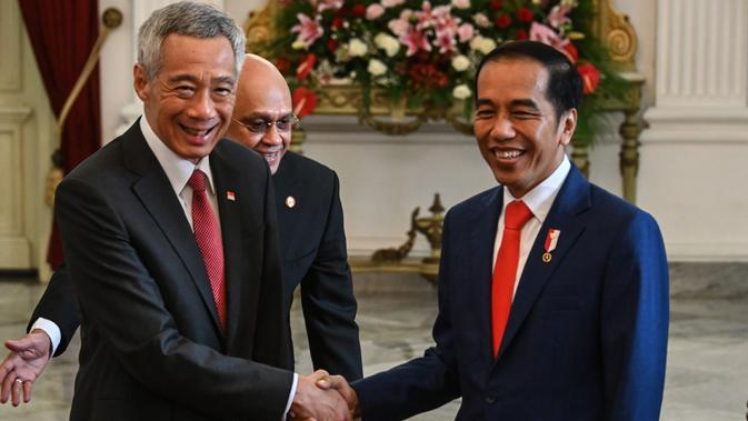 Presiden Joko Widodo bersalaman dengan Perdana Menteri Singapura Lee Hsien Loong di Istana Merdeka, Minggu (20/10/2019). Jelang pelantikan di Gedung MPR, Jokowi menerima kunjungan lima kepala negara di Ruang Kredensial Istana Merdeka, Jakarta. (AFP Photo/Bay Ismoyo)