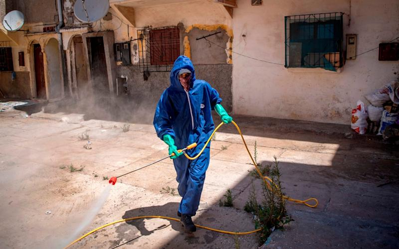 A Moroccan municipal worker disinfects outside a house in a closed street in the southern port city of Safi - FADEL SENNA/AFP via Getty Images