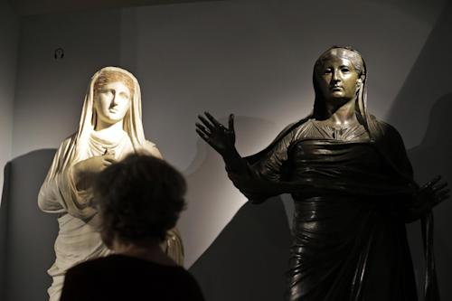 A woman looks at a statue of Empress Livia, right, found in the ruins of the ancient Roman town of Herculaneum, and one of priestess Eumachia, left, found in Pompeii, during a photo call for the upcoming exhibition entitled 'Life and death Pompeii and Herculaneum', at the British Museum in central London, Tuesday, March 26, 2013. The exhibition about the two Roman cities, buried by a catastrophic volcanic eruption of Mount Vezuvius in 79 AD, will run at the museum from March 28 to Sept. 29, 2013. (AP Photo/Lefteris Pitarakis)