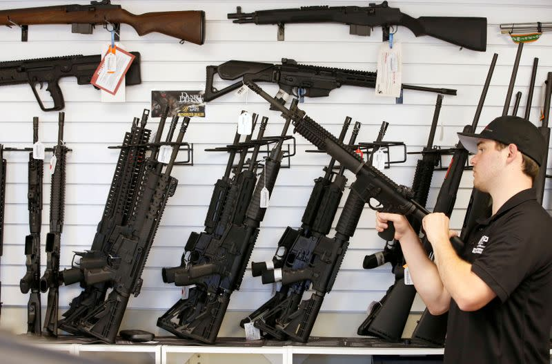 """FILE PHOTO: Salesman Ryan Martinez clears the chamber of an AR-15 at the """"Ready Gunner"""" gun store In Provo"""