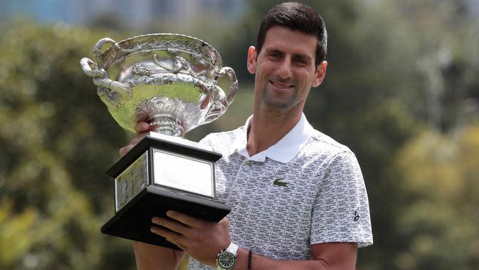Petenis Serbia, Novak Djokovic berpose dengan piala juara tunggal putra Australia Terbuka 2020 saat sesi pemotretan di Royal Botanic Gardens Victoria, Melbourne, Australia, Senin (3/2/2020). Djokovic sudah mengoleksi sebanyak 17 gelar grand slam dengan kemenangan kali ini. (AP Photo/Dita Alangkara)