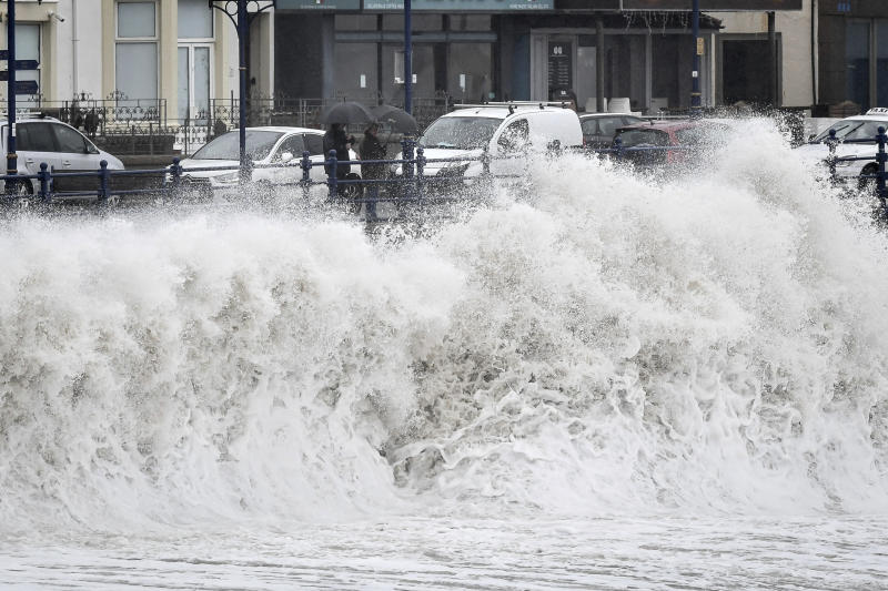 People watch waves pound against the harbour wall at Porthcawl in Wales, as Storm Dennis sweeps across the country, Saturday Feb. 15, 2020.  Enormous waves  are churning across the North Atlantic as Britain braces for a second straight weekend of wild winter weather and flooding. (Ben Birchall/PA via AP)