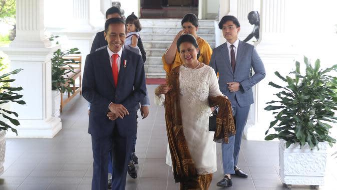 Presiden Joko Widodo bersama ibu negara Iriana didampingi putra putrinya bersiap meninggalkan Istana Merdeka menuju gedung DPR, Jakarta, Minggu (20/10/2019). Jokowi bersama keluarga menuju DPR untuk dilantik menjadi presiden untuk kedua kalinya. (Liputan6.com/Angga Yuniar)