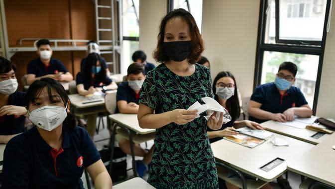 Seorang guru membagikan masker kepada siswa di dalam kelas di sekolah Marie Curie di Hanoi, Senin (4/5/2020). Vietnam membuka kembali aktivitas sekolah yang ditutup selama tiga bulan setelah dilaporkan tidak ada kasus virus corona COVID-19 baru hingga Sabtu, 2 Mei 2020. (Manan VATSYAYANA/AFP)
