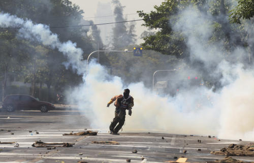 An anti-government protester runs away from tear gas canister fired by riot police near a gymnasium in Bangkok, Thailand, Thursday, Dec. 26, 2013. Officers fired tear gas and rubber bullets toward protesters trying to force their way into a sports stadium where candidates were gathering to draw lots for their position on polling papers.(AP photo/Sakchai Lalit)