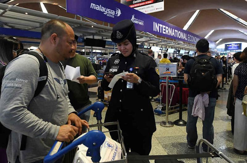 An policewoman assists a passenger at KLIA in Sepang August 23, 2019. — Bernama pic