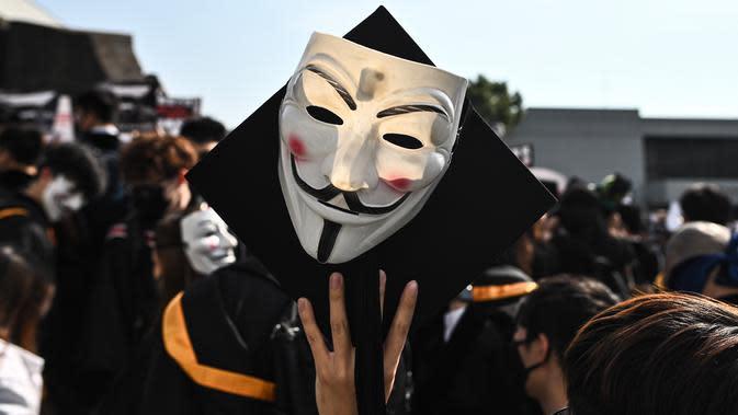 Mahasiswa mengenakan topeng Guy Fawkes selama aksi protes pada upacara kelulusan mereka di Chinese University of Hong Kong, Hong Kong, Kamis (7/11/2019). Sekitar seribu mahasiswa mengabaikan larangan mengenakan topeng yang dikeluarkan pemerintah pada Oktober 2019. (Philip FONG / AFP)