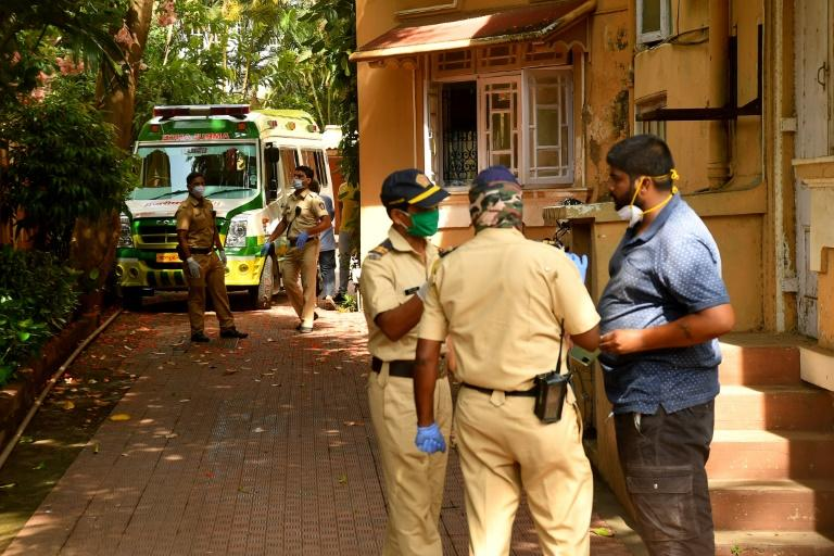 Police stand near the ambulance carrying the body of Indian Bollywood actor Sushant Singh Rajput after he took his own life, at his residence in Mumbai