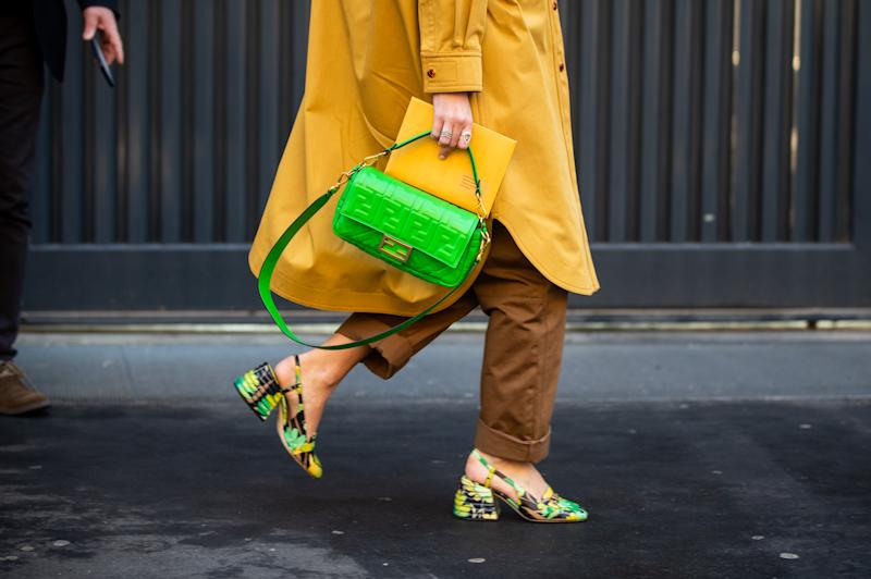 MILAN, ITALY - JANUARY 13: Estelle Pigault seen wearing yellow coat, yellow brown two tone overall, green Fendi bag and shoes with jungle print outside Fendi during Milan Fashion Week Fall/Winter 2020/2021 on January 13, 2020 in Milan, Italy. (Photo by Christian Vierig/Getty Images)